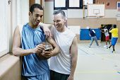 Two male basketball players with palm pilot