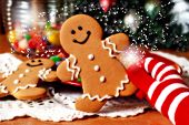 Christmas Magic.  Holiday still life of colorful gloved hand holding a smiling gingerbread man with