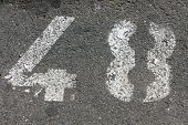 Close Up Detail Of A Number Forty Eight Painted In White On Asphalt