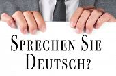 a man wearing a suit holding a signboard with the sentence sprechen sie deutsch? do you speak german