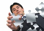 stock photo of peculiar  - business man arranging puzzle pieces - JPG