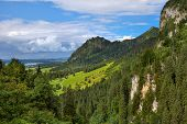 View of sunlit green meadow surrounded by forest-covered mountains under beautiful cloudy sky in Bavaria, Germany.
