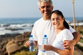 fit mature couple drinking water at the beach after exercise