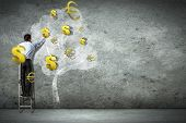 Businessman on ladder pointing at illustrated money tree