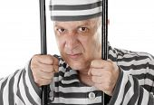 stock photo of prison uniform  - Angry convict prisoner jailbird behind bars - JPG