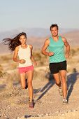 Running couple - runners jogging on trail run path outside in beautiful nature. Asian woman runner a