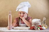 Little girl making pizza - preparing the dough and other ingredients