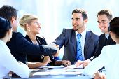 stock photo of leader  - Two business colleagues shaking hands during meeting - JPG