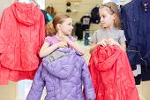 Two cute girls try on clothes in a store childrens clothes, focus on left girl
