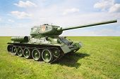 Old legendary Tank T-34/85 at green field at sunny summer day.