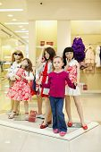 Little girl performs one of fashion dolls, standing together with group of dressed mannequins