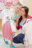 Smiling little girl and her mother cheek to cheek in clothing store, hangers with clothes in their hands