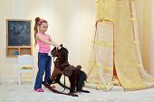 Little girl plays with hobbyhorse in play room
