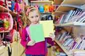 Little girl stands in school department of store, holding several notebooks
