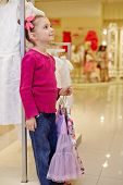 Little girl stands leaning on rack and holds hangers with light-violet skirt and flower-patterned blouse