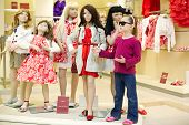 Little girl in dark sunglasses stands together with group of dressed mannequins and performs one of them