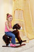 Little girl rocks on hobbyhorse in play room