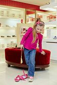 Little girl tries on new shoe with putting out tongue of diligence in store