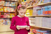 Little girl views envelopes in book department of store