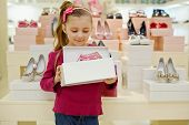 Little girl stands and holds open box with pink shoes in shoe store