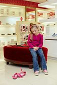 Little girl sits on ottoman in new shoes and looks at old pair