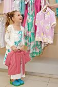 Little girl stands holding hanger with pink jacket and talks something to mother who shows another jacket