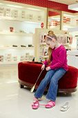 Little girl puts on shoe, helping herself by shoehorn in store
