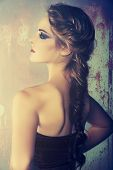 stock photo of braids  - beautiful young woman with blond red hair in fishtail braid and dramatic eye makeup - JPG