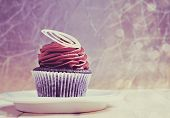 retro style chocolate cupcake with chocolate mousse cream icing on grunge wooden background with cop