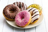 stock photo of sprinkling  - various donuts on kitchen table - JPG