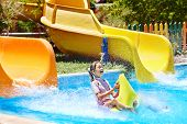Child on water slide at aquapark. Summer holiday..