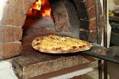 stock photo of oven  - Gourmet Pizza coming out of wood fired Pizza Oven in restaurant - JPG