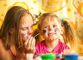 stock photo of little sister  - Funny little sisters playing with painting - JPG