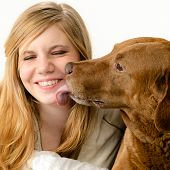 stock photo of snuggle  - Portrait of a pretty girl snuggling with her dog - JPG