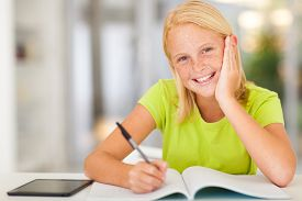 stock photo of pre-adolescents  - happy teen schoolgirl doing homework at home - JPG