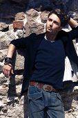 foto of friendship belt  - stylish young man posing against a stone wall - JPG