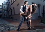 stock photo of tango  - Young couple perform dance steps on the street - JPG