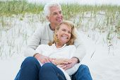 Romantic senior man and woman relaxing on sand at the beach