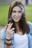 foto of teen smoking  - Happy teen girls having good fun time outdoors smoking - JPG