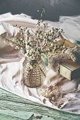 Spring white flower branches on grunge table with silk cloth and a book with lace and pearl wedding keepsakes