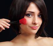 Woman Applying Blusher The Big Red Brush. Closeup Portrait