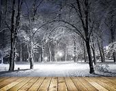 Winter park in the evening covered with snow with a row of lamps with wooden floor
