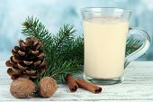Cup of eggnog with fir branches on table on bright background
