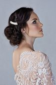 stock photo of lace  - Beautiful young bride with wedding makeup in romantic lace dress on studio background - JPG