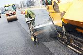 image of vibrator  - Worker operating asphalt paver machine during road construction and repairing works - JPG