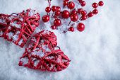 Two beautiful romantic vintage red hearts with mistletoe berries on a white snow background. Christm