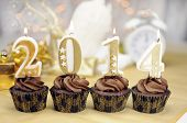 stock photo of icing  - Happy New Year chocolate cupcakes with 2014 candles against bokeh Christmas lights - JPG