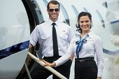 stock photo of flight attendant  - Portrait of happy confident airhostess and pilot standing on private jet - JPG