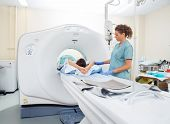 Nurse preparing patient for CT scan in hospital room