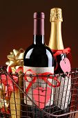 Closeup of a wire shopping basket with Valentines Presents. Vertical Format on a light to dark red background. Items include champagne, wine, gift boxes. The bottles have heart shaped gift tags.